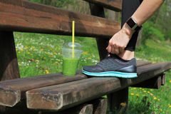 Woman runner drinking green vegetable smoothie resting after workout. Sport, Fitness people using smart watch Royalty Free Stock Photography