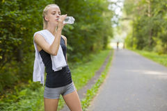 Woman runner drinking water after running Stock Images