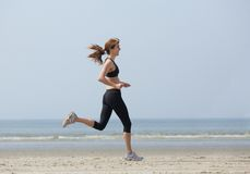 Woman runner enjoying exercise at the beach Stock Photos