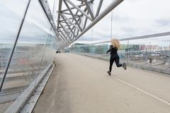 Woman runner during fast running exercise in modern city at cloudy day. stock images