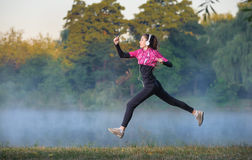 Woman runner on foggy morning near lake Stock Image