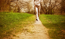 Woman runner in a green forest. Stock Photo
