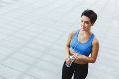 Woman runner is having break, drinking water Stock Photo