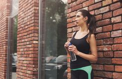 Woman runner is having break, drinking water royalty free stock photos