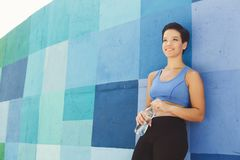 Woman runner is having break, drinking water. Young woman runner is having break, drinking water while jogging in city, leaning at blue painted wall, copy space Royalty Free Stock Image