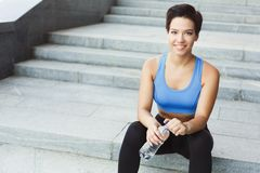 Woman runner is having break, drinking water. Young woman runner is having break, drinking water while jogging in city, sitting on staircase, smiling at camera Royalty Free Stock Images