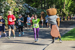Woman runner high-fives OSU mascot during 5K charity run Royalty Free Stock Photo