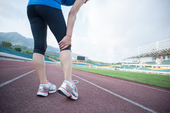Woman runner  hold her injured leg Stock Photo