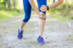 Woman runner hold her injured leg after running in forest trail. Royalty Free Stock Photo