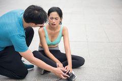 Woman runner hold her pain sprained ankle leg. Asian sad sport female runner hurt and hold her painful sprained ankle while boyfriend check pain severity Royalty Free Stock Photo
