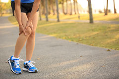 Woman runner hold her sports injured knee Stock Images