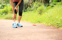 Woman runner holder her sports injured knee Stock Photos