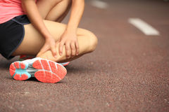 Woman runner holder her twisted ankle Stock Photo