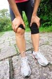 Woman runner injured knee Stock Photos