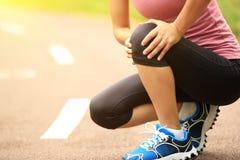 Woman runner injured knee Stock Image