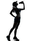 Woman runner jogger drinking. One caucasian woman runner jogger drinking in silhouette studio isolated on white background Stock Image