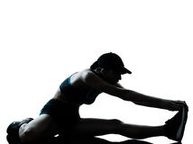 Woman runner jogger stretching legs warming up silhouette Stock Image