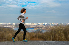 Woman runner jogging with beautiful city view, running outdoors Stock Images