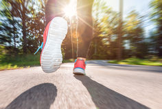Woman runner jogging down the road Stock Photos