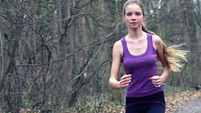 Woman runner is jogging on forest path in  park. stock video