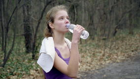 Woman runner is jogging on forest path in  park. stock footage