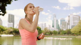 Woman runner jogging in park. Fit female sport fitness running training. Drinking water from bottle. Beautiful attractive young woman runner with a ponytail stock video