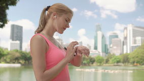 Woman runner jogging in park. Fit female sport fitness running training. Using smartwatch. Beautiful attractive young woman runner with a ponytail jogging in stock video footage