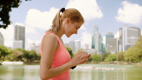 Woman runner jogging in park. Fit female sport fitness training. Making photo on her smartphone. Beautiful attractive young woman runner with a ponytail jogging stock footage