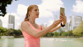 Woman runner jogging in park. Fit female sport fitness training. Making selfie on her smartphone. Beautiful attractive young woman runner with a ponytail jogging stock video footage