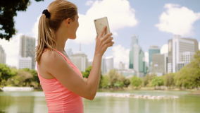 Woman runner jogging in park. Fit female sport fitness training. Talking with friend via Skype. Beautiful attractive young woman runner with a ponytail jogging stock video footage