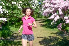 Woman runner jogging in spring park with lilac blossom, morning run outdoors, fitness and running stock image