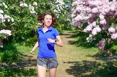 Woman runner jogging in spring park with lilac blossom, morning run outdoors, fitness and running royalty free stock image