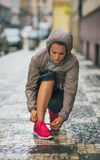 Woman runner kneeling down to tie running shoe in rain. A pop of pink colour adds a bit of spring to my step... Or at least it is supposed to. A woman jogger Royalty Free Stock Photography
