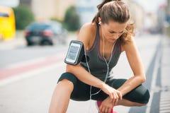 Woman runner kneeling, looking down, listening to music Stock Images