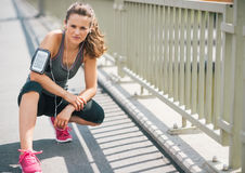 Woman runner kneeling on sidewalk in summer in urban setting Stock Photography