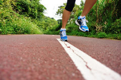 Woman runner legs running at forest trail Royalty Free Stock Photo
