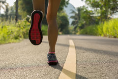 Woman runner legs running on morning tropical forest trail Royalty Free Stock Images