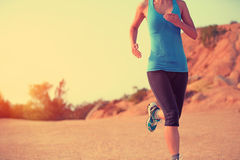 Woman runner legs running on mountain trail Stock Photos