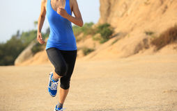 Woman runner legs running on mountain trail Royalty Free Stock Photo