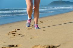 Woman runner legs in shoes on beach Royalty Free Stock Photography