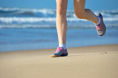 Woman runner legs in shoes on beach Stock Images