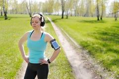 Woman runner listening to music in headphones. Stock Photo
