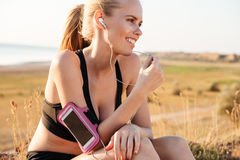 Woman runner listening to music with mobile phone in armband Royalty Free Stock Photo