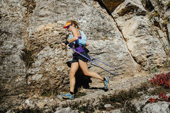 Woman runner with nordic walking sticks running trail on background of rocks Royalty Free Stock Photos