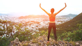 Woman runner raise hands up in the air. Female run on top of the mountain, cheering in winning gesture. Stock Photography