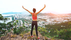 Woman runner raise hands up in the air. Female run on top of the mountain, cheering in winning gesture. Royalty Free Stock Photo