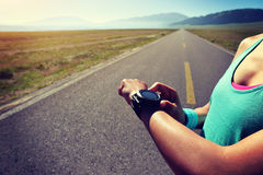 woman runner ready to run set and looking at sports smart watch Royalty Free Stock Images