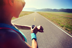 Woman runner ready to run set and looking at sports smart watch Stock Photo