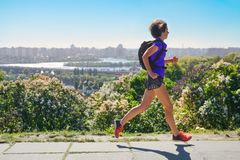 Woman runner run commutes to work with backpack, city morning run commuting and fitness concept royalty free stock images