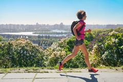 Woman runner run commutes to work with backpack, city morning run commuting and fitness concept stock photography